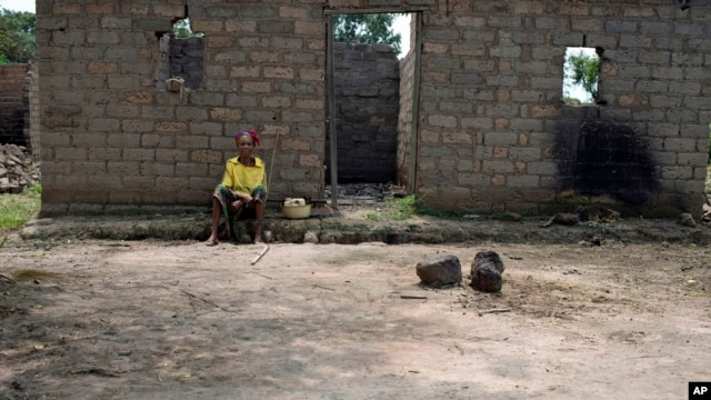Julienne Mbetidemo sits outside the remains of her home, burned by Seleka rebels, in the village of Ngangue, 10 kilometers (6 miles) from Mbres, Central African Republic, July 27, 2013.