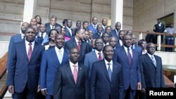 The new Ivory Coast government pose with President Alassane Ouattara after a council, at the Presidential Palace in Abidjan June 3, 2011.