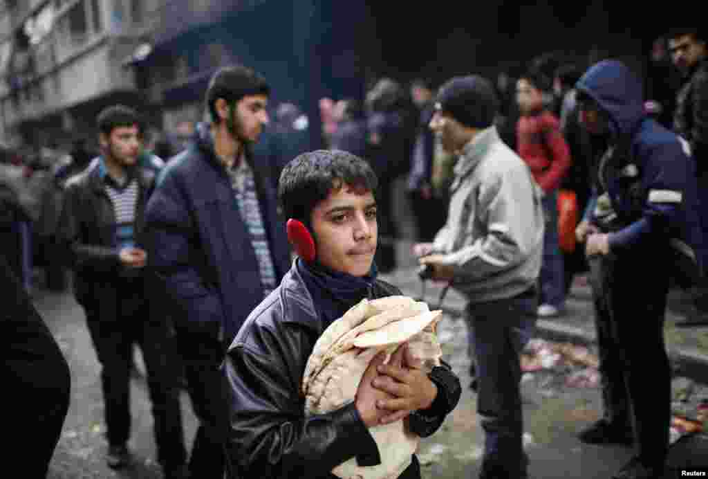 A boy holds pita bread as others stand in line outside a bakery in Aleppo, Syria, December 21, 2012.