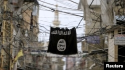 FILE - An Islamic State flag hangs amid electric wires over a street in southern Lebanon, Jan. 19, 2016.