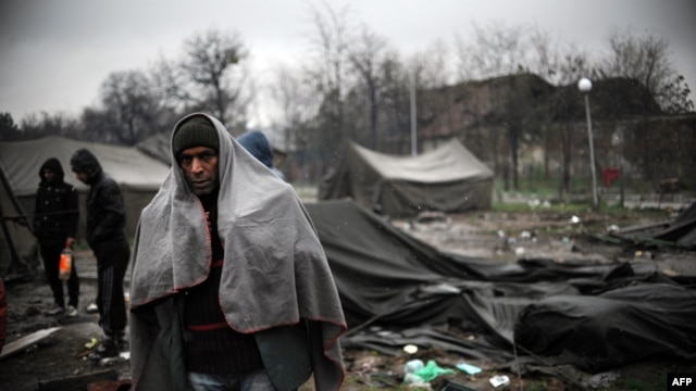 A man stands by tents as snow falls in a refugee camp set in the Bulgarian town of Harmanli, south-east of Sofia, on November 27, 2013. AFP