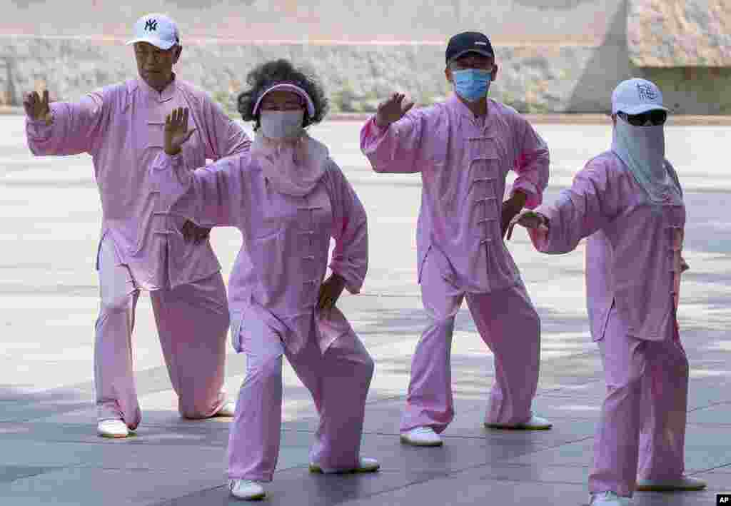 Taiji practitioners, some wearing masks, go through their routine in Beijing.