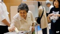 Seorang peserta pemilu parlemen Jepang memasukkan surat suaranya ke kotak suara di salah satu TPS di Tokyo, Minggu (21/7).