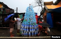 Victims of super Typhoon Haiyan decorate their improvised Christmas tree with empty cans and bottles at the ravaged town of Anibong, Tacloban city, central Philippines Dec. 24, 2013, a month after Typhoon Haiyan battered central Philippines.