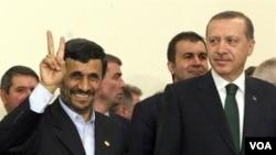 "Presiden Iran Mahmoud Ahmadinejad mengacungkan tanda kemenangan (""Victory"") saat dicapainya kesepakatan pertukaran uranium dengan PM Turki Erdogan di Teheran, 17 Mei 2010 ."