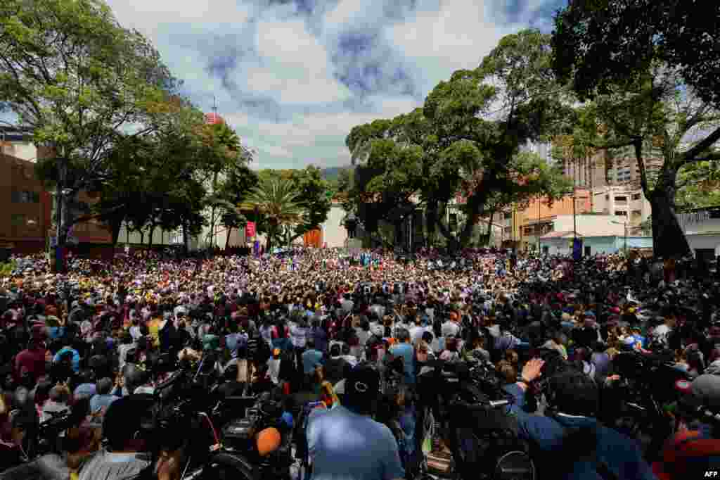 Opposition supporters gather to listen to Venezuela's National Assembly head and the country's self-proclaimed 'acting president' Juan Guaido, at Bolivar Square in Chacao, eastern Caracas.