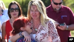 FILE - In this Feb. 14, 2018, file photo, Mechelle Boyle, right, embraces Cathi Rush as they wait for news after reports of a shooting at Marjory Stoneman Douglas High School in Parkland, Fla. The image become a symbol of the Parkland school shooting. (AP