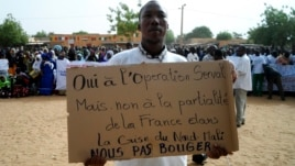 A man holds up a placard during a protest urging Mali and France to retake Kidal, Gao, May 30, 2013.