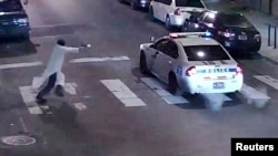 FILE - A still image from surveillance video shows a gunman approaching a Philadelphia police vehicle in which Officer Jesse Hartnett was shot shortly before midnight Jan. 7, 2016.