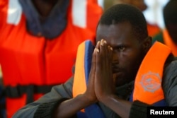 An African rescued by the Migrant Offshore Aid Station reacts as the ship Phoenix reaches Sicily's port of Pozzallo. The charity provided this courtesy photo Oct. 5, 2014.