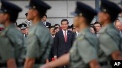 Trưởng quan Hành chính Lương Chấn Anh xem quân đội diễu hành trong lễ thượng kỳ ở Hong Kong trong khi hàng ngàn người biểu tình từ phía sau hàng rào chắn của cảnh sát la ó đòi ông từ chức.