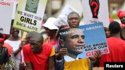 Orang-orang membawa poster menuntut dikembalikannya para siswi yang diculik militan Boko Haram di desa Chibok, Lagos (9/5/2014).