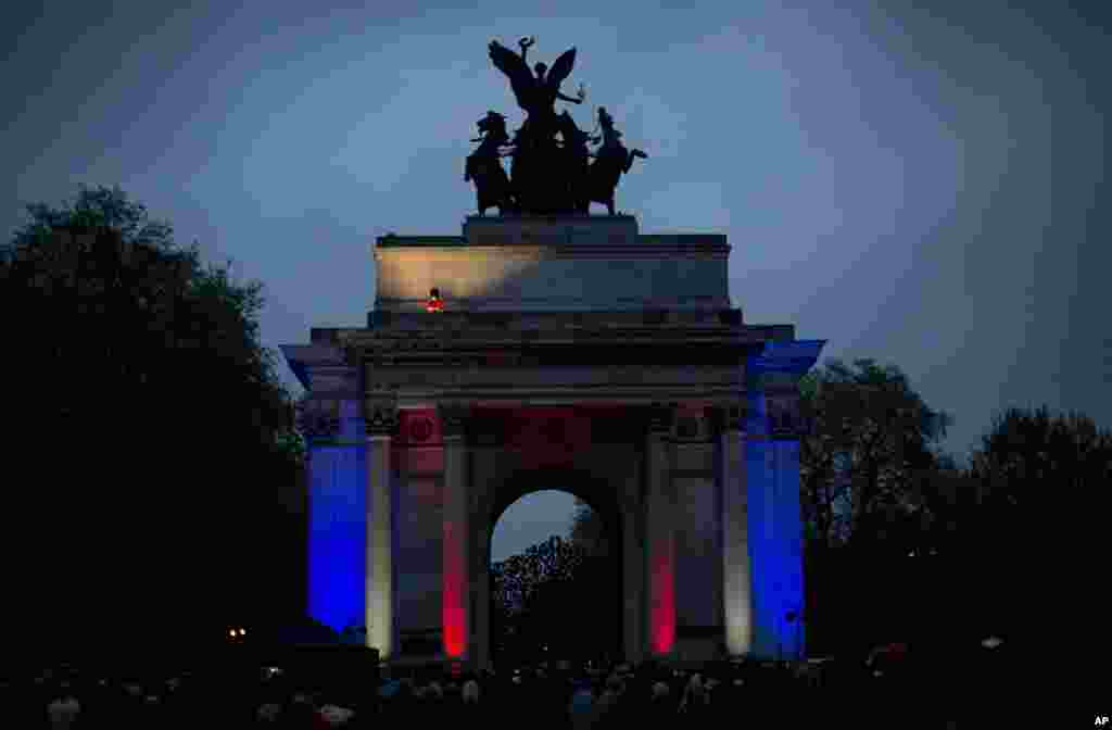 A member of the British military plays a bugle on top of the Wellington Arch before the start of two minutes of silence during a dawn service to mark the 99th Anzac Day on Hyde Park Corner in London.