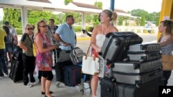 FILE - British tourists queue with their luggage to leave by charter flight from the international airport in Mombasa, Kenya.