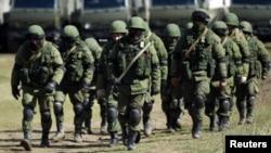 Soldados rusos sin insignias en sus uniformes cerca de su base militar en Perevalnoye, en las afueras de Simferopol.