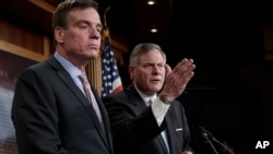 Sen. Mark Warner, D-Va., left, the vice chairman of the Senate Select Committee on Intelligence, and Chairman Richard Burr, R-N.C., right, speak to reporters about their panel's investigation of Russian interference in the 2016 election, on Capitol Hill,