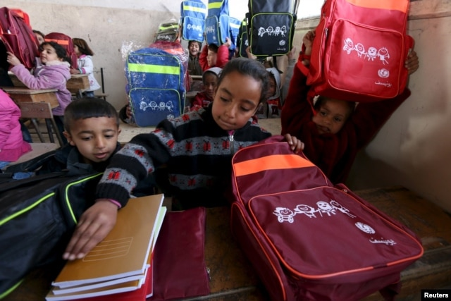 Syrian children carry bags, printed with a UNICEF logo, that they received as aid inside their classroom in Ras al-Ain city, Syria, Feb. 1, 2016.