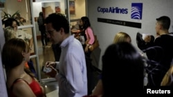 People gather at the gates of Copa Airlines headquarters in Caracas, Venezuela, April 6, 2018. Venezuela cut commercial ties with Panama, including Copa Airlines, over accusations of money laundering.