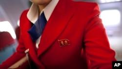 지난해 4월 중국 베이징에서 북한 평양으로 향하는 고려항공 소속 여객기 내부. 승무원이 김일성 전 주석과 김정일 전 위원장의 초상화가 나란히 들어있는 뱃지를 달고 있다. (자료사진)