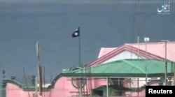 FILE - A still image taken from a video posted to a social media website by the Islamic State-affiliated Amaq News Agency on June 12, 2017, shows a black flag perched on a building in Marawi City, Philippines.
