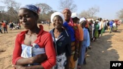 FILE: Women queue for food assistance distributed by the United Nations World Food Programme in Mwenezi, about 450 kilometers (280 miles) south of Harare, Zimbabwe, Wednesday, Sept. 9 2015.