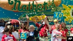 Joey Chestnut, right, is declared Nathan's Famous Fourth of July International Hot Dog Eating Contest men's competition winner, Monday, July 4, 2016, in New York.