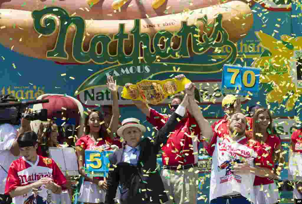 Joey Chestnut, right, is declared the men's competition winner of Nathan's Famous Fourth of July International Hot Dog Eating Contest, in New York.