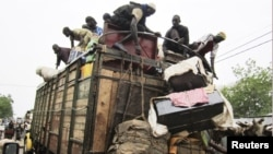People load on onto a truck carrying residents fleeing south from an Islamic insurgency in northern Mali at the trading town of Mopti.