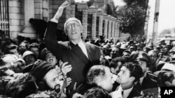 FILE - Prime Minister Mohammed Mosaddegh rides on the shoulders of cheering crowds in Tehran's Majlis Square, outside the parliament building, after reiterating his oil nationalization views to his supporters. Once expunged from its official history, documents outlining the U.S.-backed 1953 coup in Iran have been quietly published by the State Department.