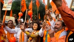FILE - A man stands dressed as Hindu god Ram, center, as activists of right wing Hindu groups shout slogans demanding that a temple of Hindu god Ram be made at Ayodhya on the anniversary of the Babari Mosque demolition in New Delhi, India, Dec. 6, 2018.