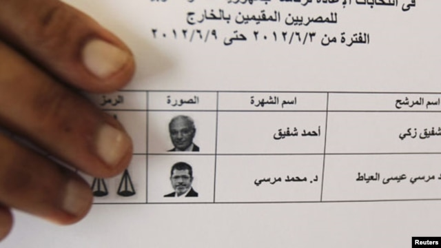 An Egyptian expatriate displays his ballot before casting his vote.
