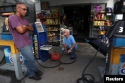 Men buy gasoline in Maunabo, Jan. 27, 2018.
