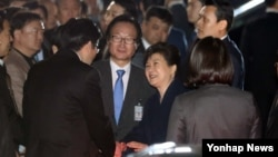 한국의 박근혜 전 대통령이 12일 오후 청와대를 떠나 서울 삼성동 사저에 도착한 직후 지지자들과 악수하고 있다.