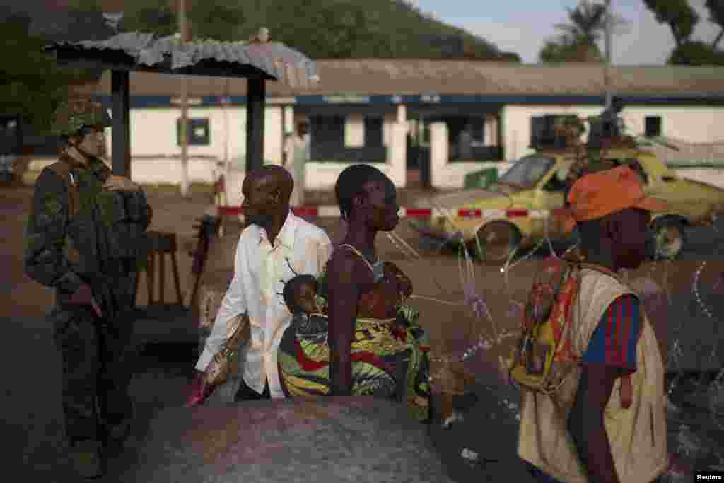 Pessoas passam por posto de controlo gerido pelas forças de paz francesas e pela polícia local no Quilómetro 12 em Bangui, Março 3, 2014.