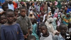 FILE - In this Tuesday Sept. 9, 2014 file photo, civilians who fled their homes following an attack by Islamist militants in Bama, take refuge at a school in Maiduguri, Nigeria. Attacks by Islamic extremist group Boko Haram in northeastern Nigeria and neighboring countries have forced more than 1 million children out of school.