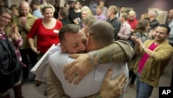 FILE - Chris Serrano, left, and Clifton Webb embrace after being married, as people wait in line to get licenses outside of the marriage division of the Salt Lake County Clerk's Office in Salt Lake City, Utah, Dec. 20, 2013.