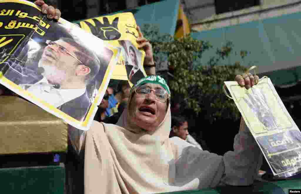 4일 무르시 전 이집트 대통령의 지지자가 카이로 고등법원 앞에서 포스터를 들고 시위하고 있다.