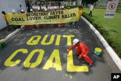 "FILE - Activists from the environmentalist group Greenpeace paint the words ""Quit Coal"" on the driveway of the Department of Energy at Manila's Taguig city Tuesday June 3, 2008 in another protest urging the Philippine Government to stop building and expansion of coal plants and promote instead alternative sources of energy to stop climate change."