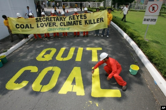 """FILE - Activists from the environmentalist group Greenpeace paint the words """"Quit Coal"""" on the driveway of the Department of Energy at Manila's Taguig city Tuesday June 3, 2008 in another protest urging the Philippine Government to stop building and expansion of coal plants and promote instead alternative sources of energy to stop climate change."""