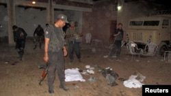 Seorang anggota pasukan keamanan Pakistan memeriksa lokasi pemboman di kota Kulachi, provinsi Khyber Pakhtunkhwa (16/10).