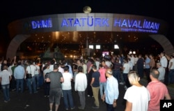People stand in front of a tank parked in the entrance to Istanbul's Ataturk airport, July 16, 2016. Members of Turkey's armed forces said they had taken control of the country, but Turkish officials said the coup attempt had been repelled early Saturday, state-run media said.