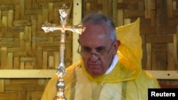"FILE - Pope Francis, shown in a rain poncho during a Mass near the Tacloban airport, said during his trip this month to the typhoon-vulnerable Philippines that ""man has gone too far damaging the environment."""