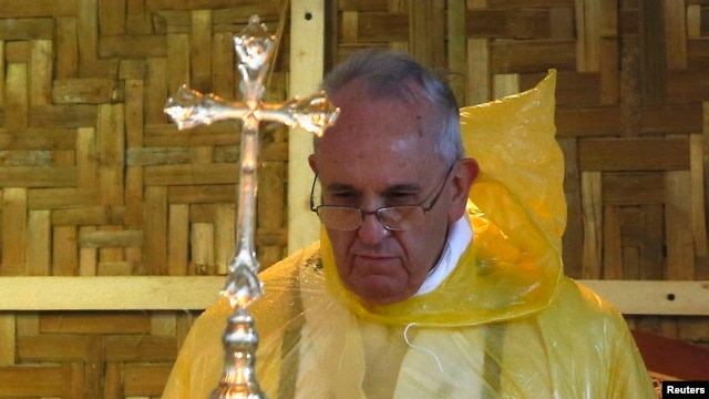 """FILE - Pope Francis, shown in a rain poncho during a Mass near the Tacloban airport, said during his trip this month to the typhoon-vulnerable Philippines that """"man has gone too far damaging the environment."""""""