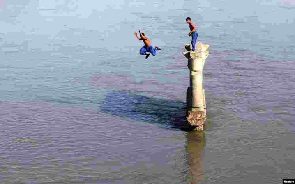 پشاور میں ایک لڑکا گرمی کی شدت کو کم کرنے کے لیے دریا میں چھلانگ لگا رہا ہے۔