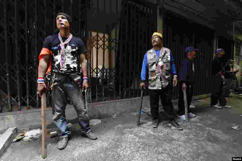 Anti-government protesters prepare to enter an abandoned building to search for a person who threw an explosive device, Bangkok, Jan. 17, 2014.