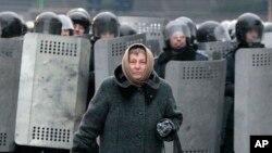 우크라이나 수도 키에프에서 21일에도 반정부 시위가 계속된 가운데, 한 여성이 진압 경찰 앞을 지나고 있다.