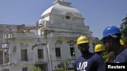 Workers from U.S. actor and Haiti's ambassador-at-large Sean Penn's charity J/P HRO (J/P Haitian Relief Organization) stand in front of the collapsed cupola of the condemned National Palace in Port-au-Prince, September 07, 2012.