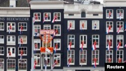 FILE - Dutch national flags hang from windows overlooking Central Station in Amsterdam, The Netherlands, April 28, 2013. Voters in the country where the modern European Union was born are now increasingly looking to reclaim some of their sovereign rights they feel the EU bureaucracy in Brussels has taken away from them.
