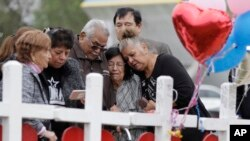 Family and friends gather around a makeshift memorial for the victims of the First Baptist Church shooting at Sutherland Springs Baptist Church in Sutherland Springs, Texas, Nov. 10, 2017.