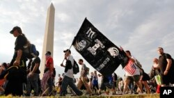 Juggalos, as supporters of the rap group Insane Clown Posse are known, march past the Washington Monument as they head towards the Lincoln Memorial in Washington during a rally, Sept. 16, 2017.